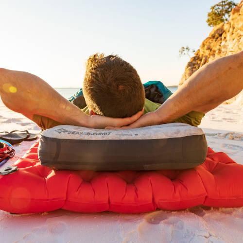 Ein Mann liegt auf einer Isomatte am Strand